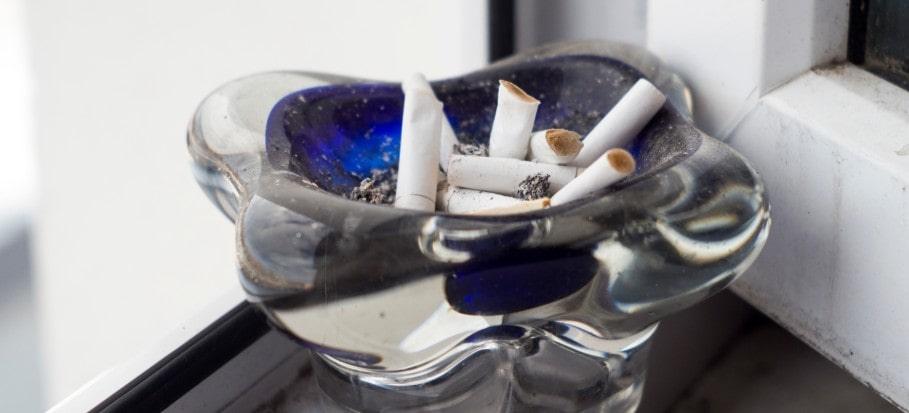 Ashtray with cigarettes on a window