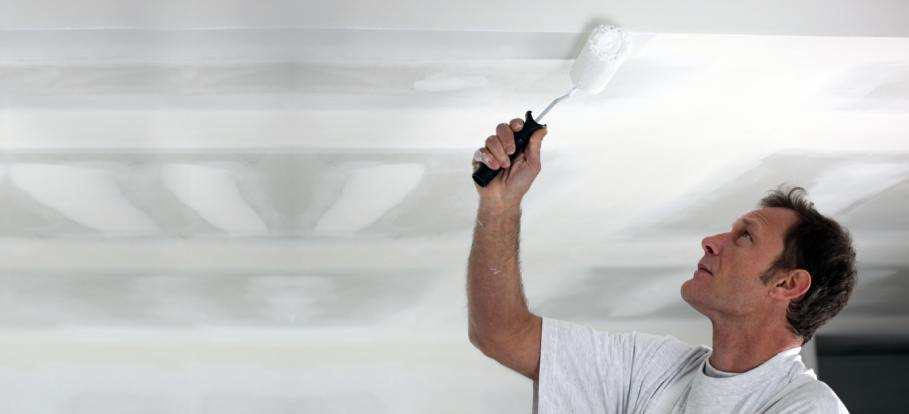 Professional painter working on a newly-plastered ceiling