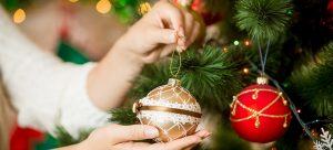 woman putting a bauble on a christmas tree