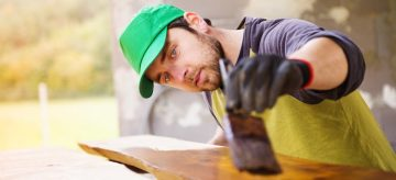 Professional painter working working on a varnished wood furniture
