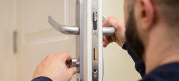 A professional locksmith is fitting a thumb turn lock