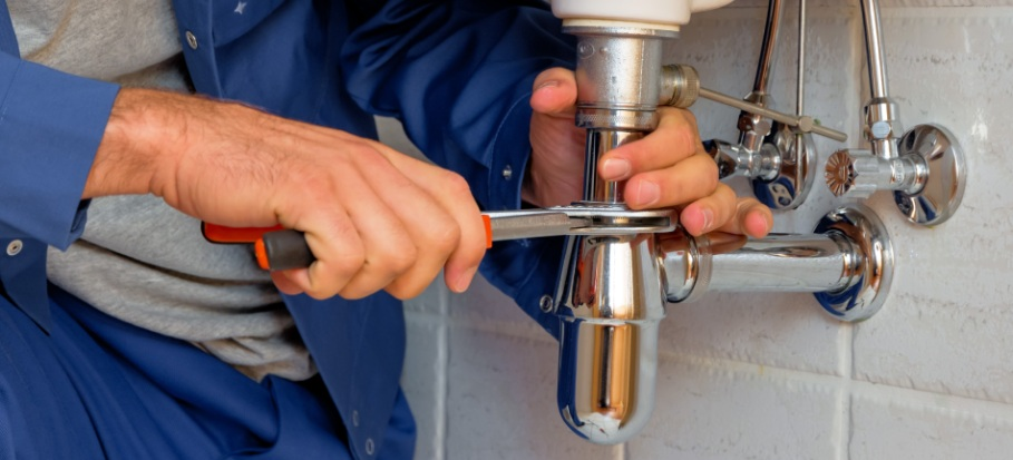A plumber fixes a sink pipe amid the coronavirus breakdown